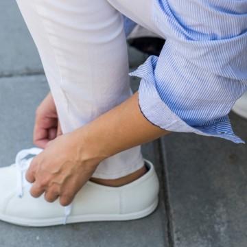 С бели джинси, риза на сини райета и спортни обувки