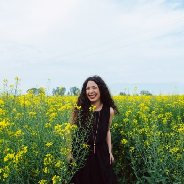 С черна рокля в бохо стил и бляскаво колие сред най-слънчевото поле