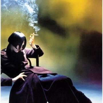 Една жена на 40, която пуши, гледайки листопада